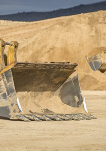 Stock phtoo of a front loader with a giant mountain of dirt behind it.